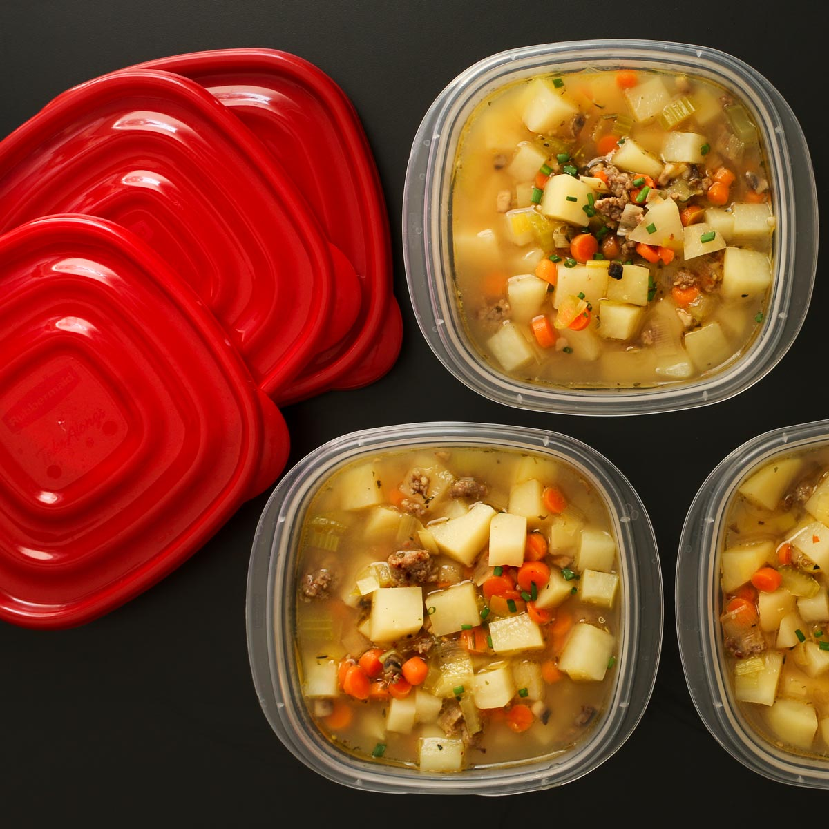 potato soup with sausage in meal prep containers with lids nearby.