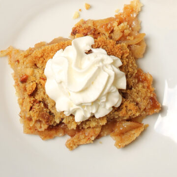 square of apple pie on white plate topped with whipped cream.