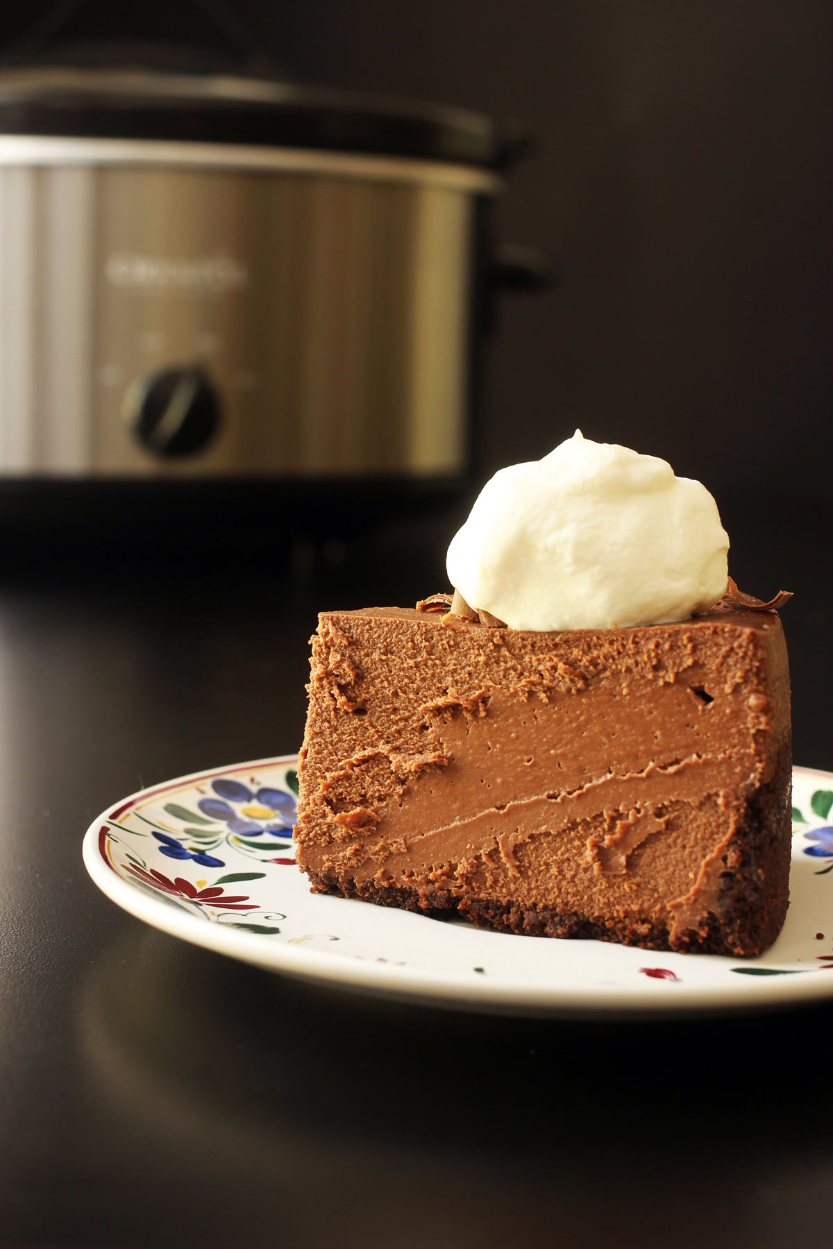 slice of cheesecake on plate in front of slow cooker.