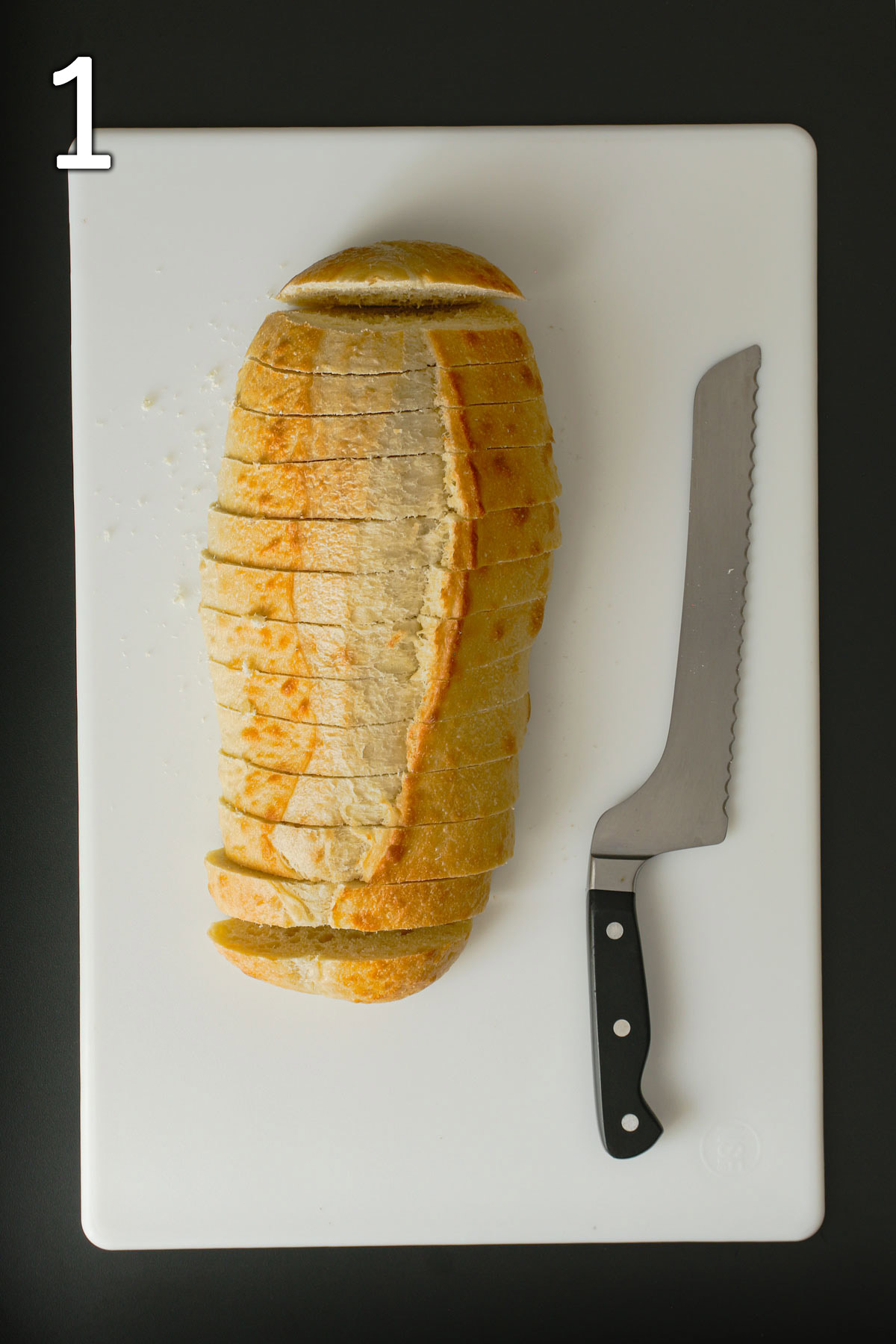 bread loaf cut into slices on white board next to bread knife.