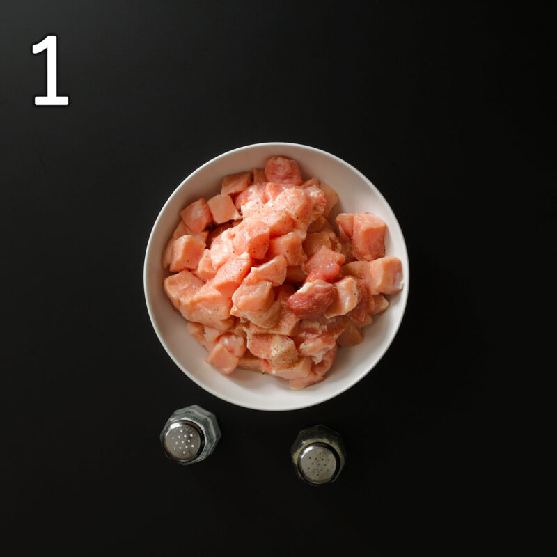 seasoning pork cubes with salt and pepper in a white bowl on a black table top.