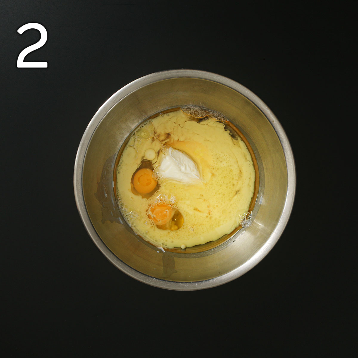 milk, juice, oil, yogurt, and eggs in another steel mixing bowl on black work surface.
