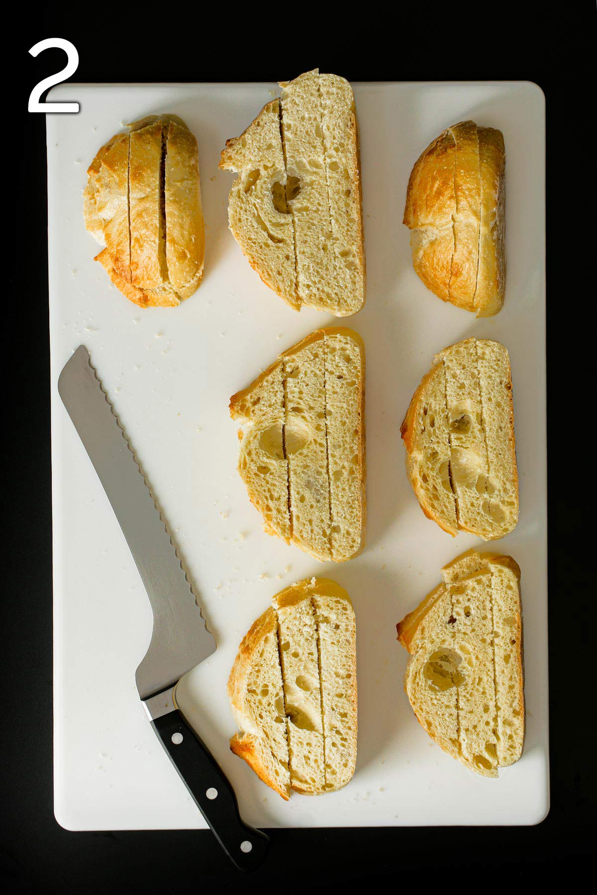 stacked bread slices cut into strips on white board next to bread knife.
