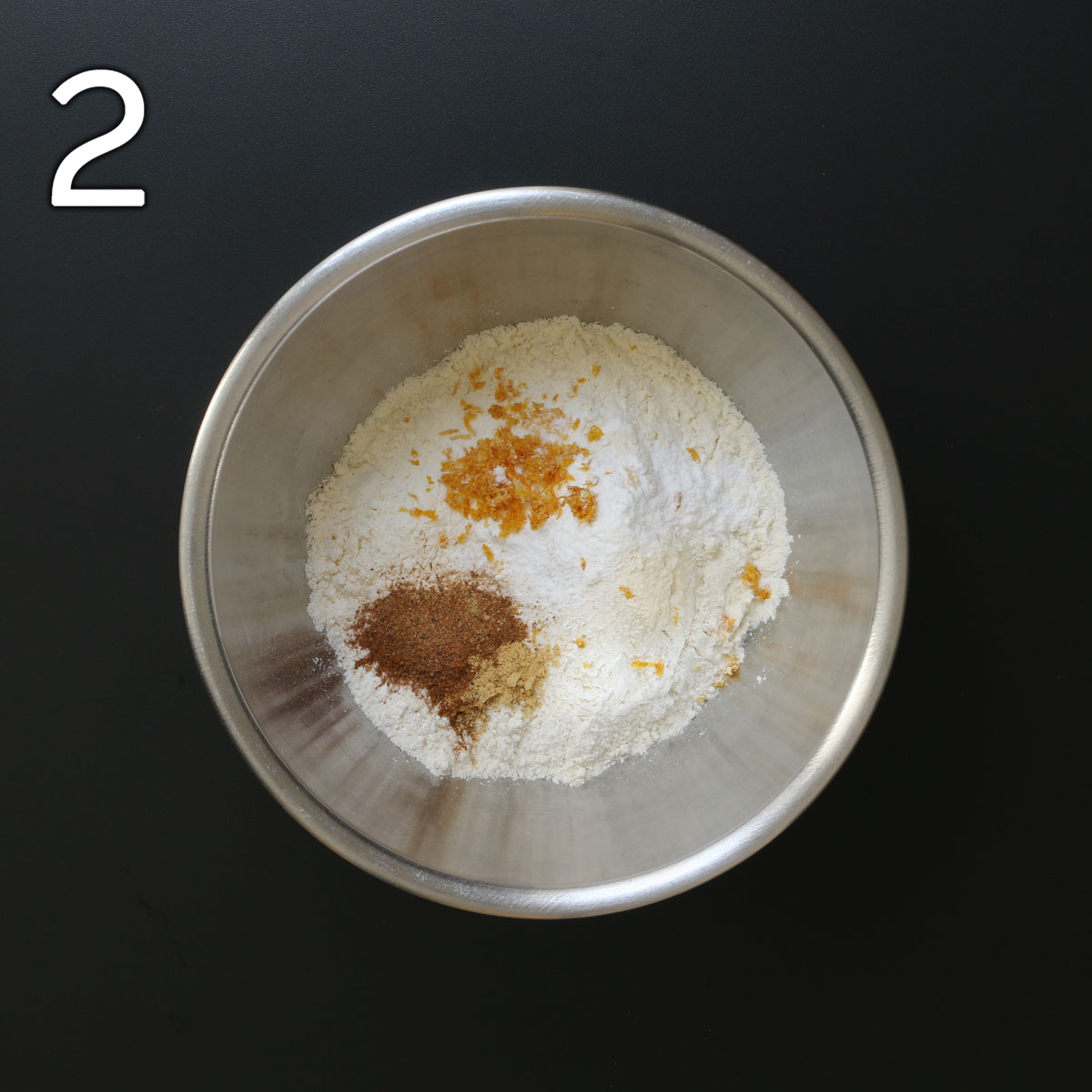 flour, spices, and zest in metal mixing bowl.