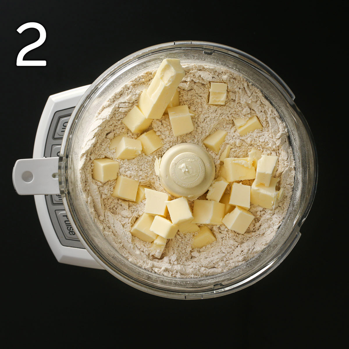 adding butter cubes to food processor.