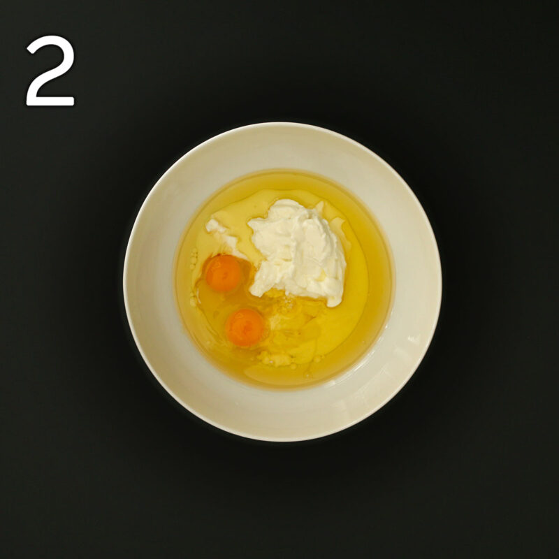 eggs, oil, yogurt, and milk in large white mixing bowl.