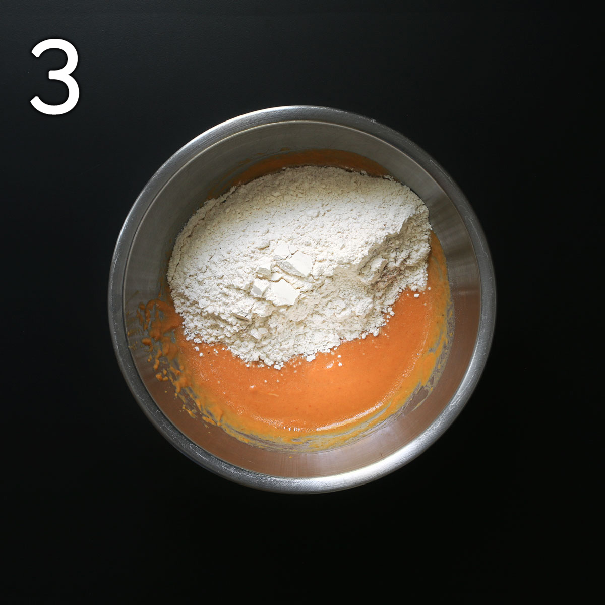 adding dry ingredients to wet ingredients in metal bowl.