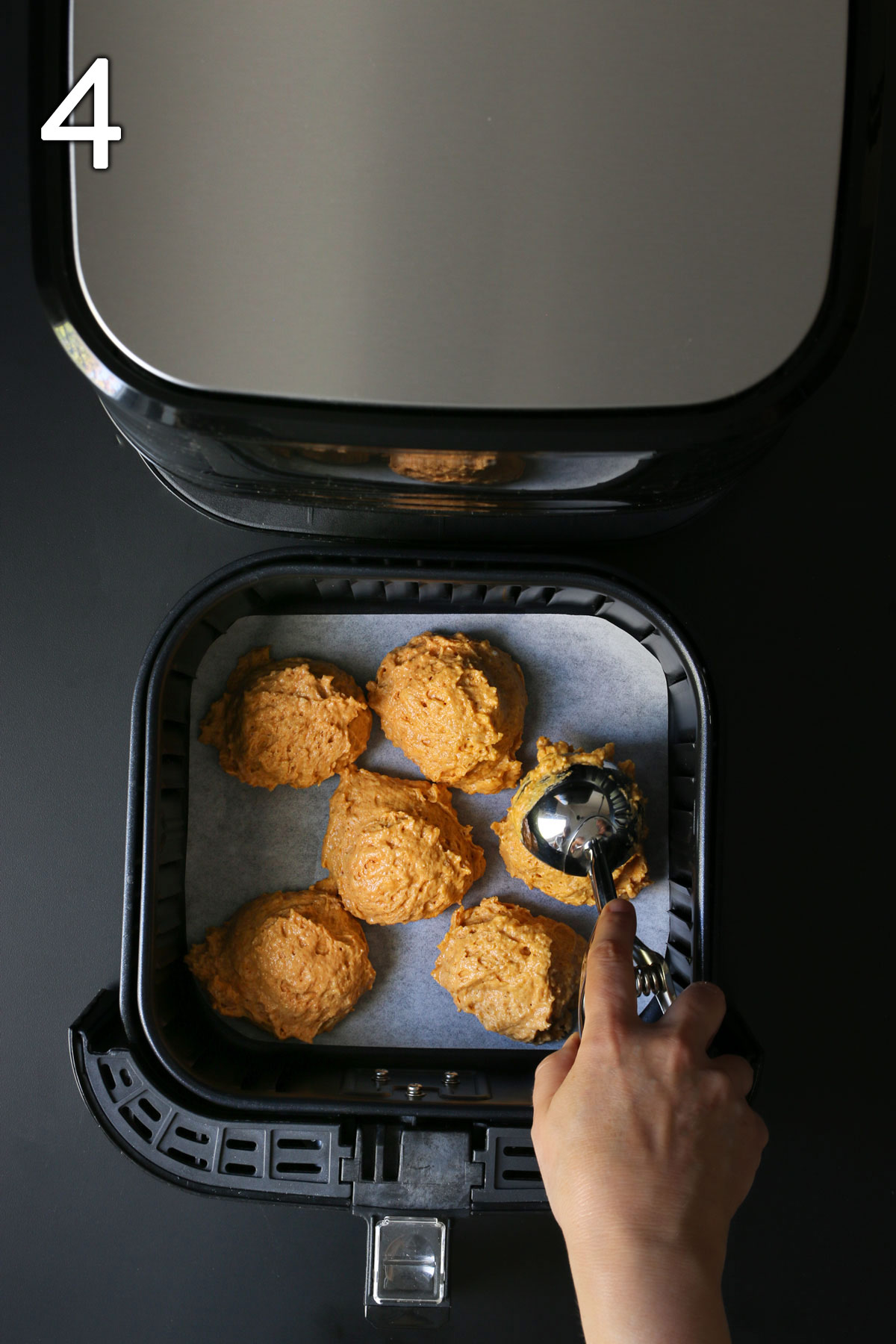 scooping batter into lined air fryer basket.