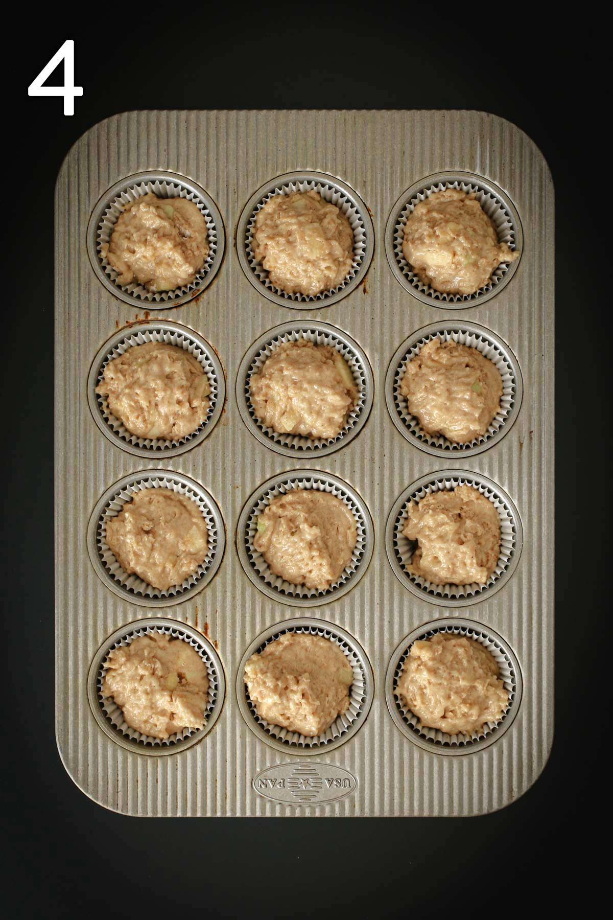 muffin batter scooped into paper lined muffin tin on black table.