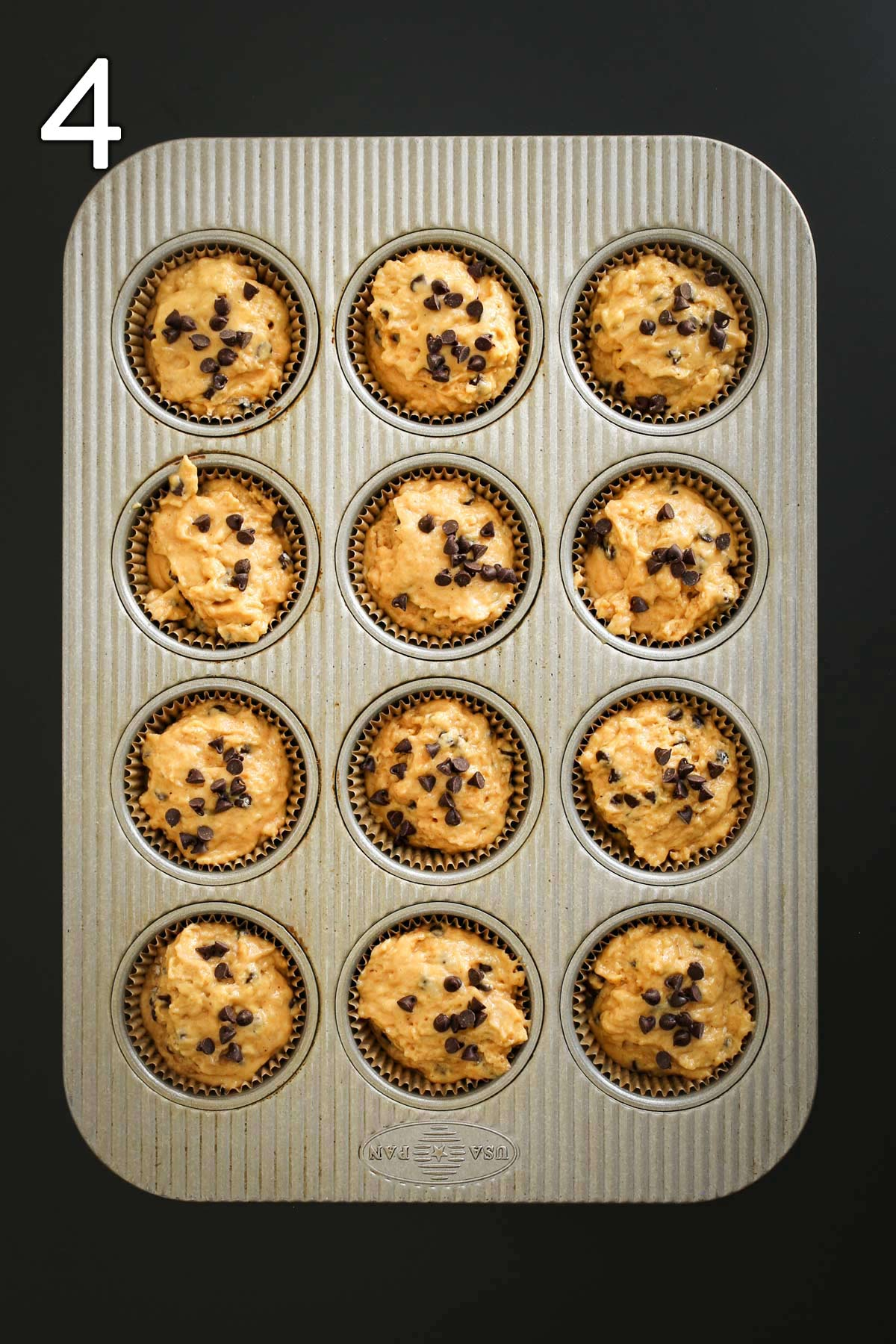 pumpkin muffin batter in tin topped with chocolate chips.