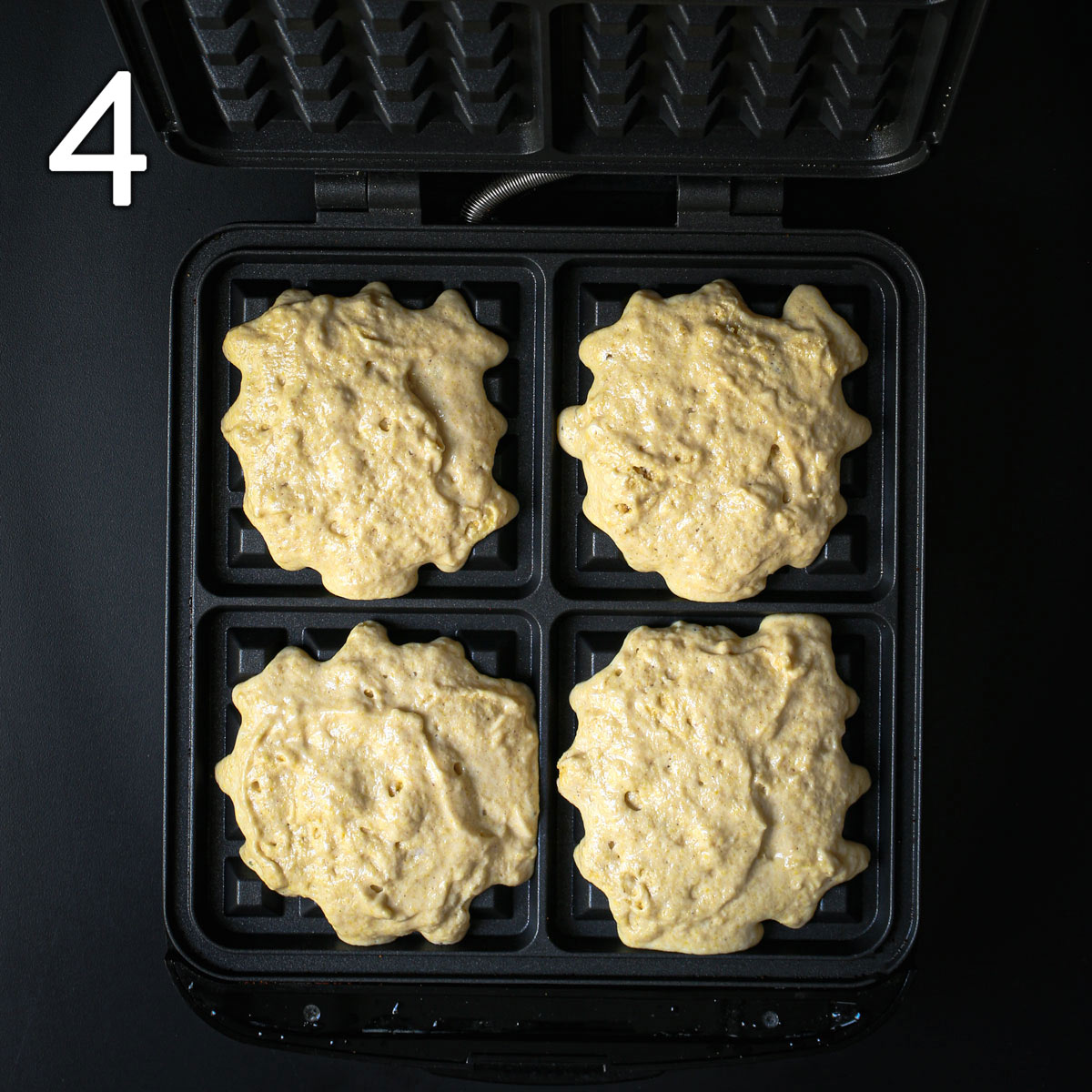 cornbread waffle batter scooped into each of four sections of a belgian waffler.