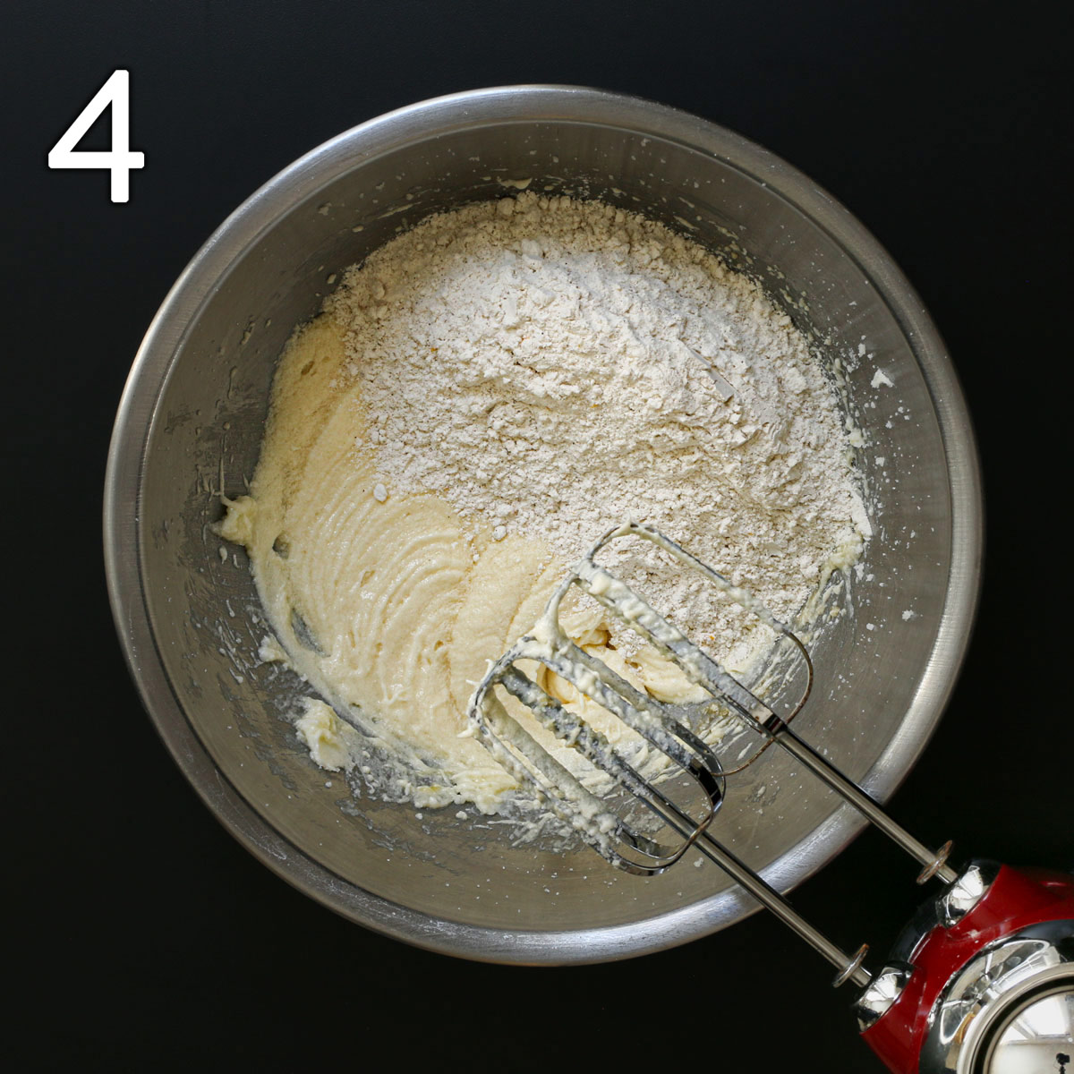 adding dry mixture to wet ingredients for pear cake in mixing bowl.