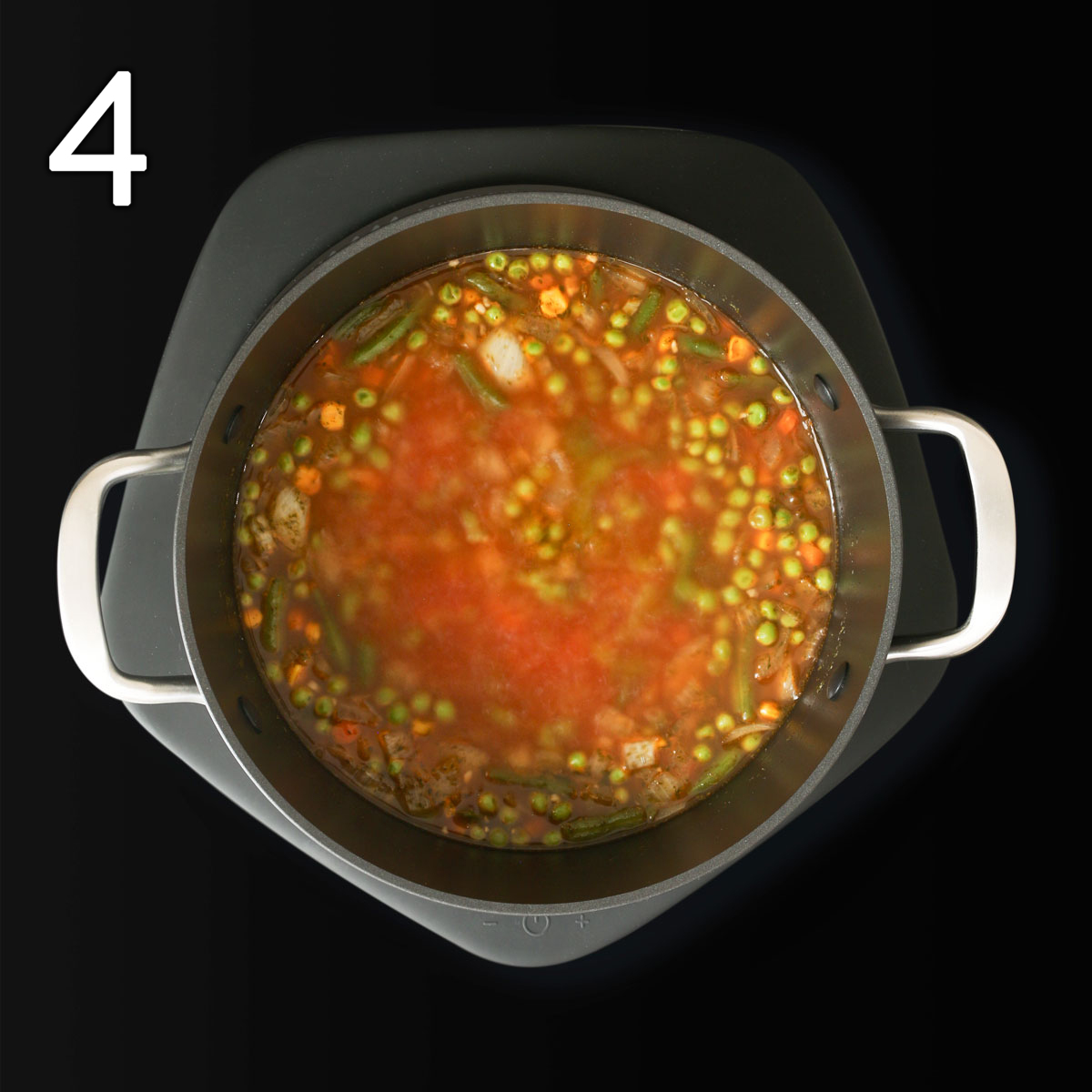 vegan soup with alphabet noodles simmering on stovetop.