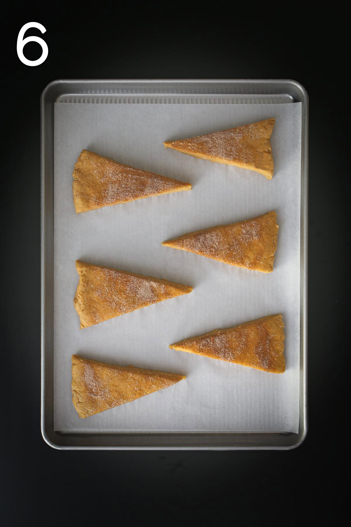 six scone triangles laid out on a baking sheet.
