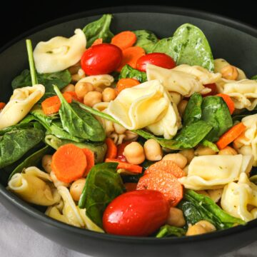 close up of pasta salad with tortellini in black bowl.
